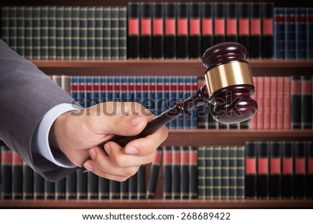 Male Judge Hand Striking The Wooden Gavel In A Courtroom - stock photo