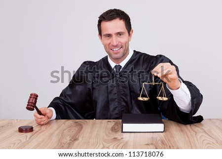 Male Judge Holding Gavel and Scale In Courtroom - stock photo