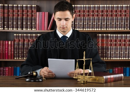 Male judge reading documents while sitting at desk in courtroom - stock photo