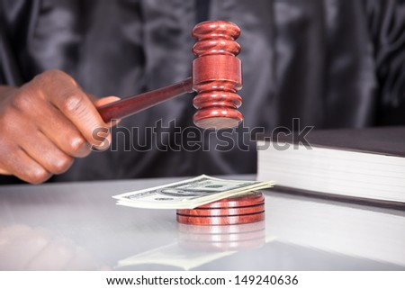 Male Judge Striking The Gavel Dollar Note In A Courtroom - stock photo