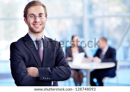 Male leader looking at camera with his partners working on background