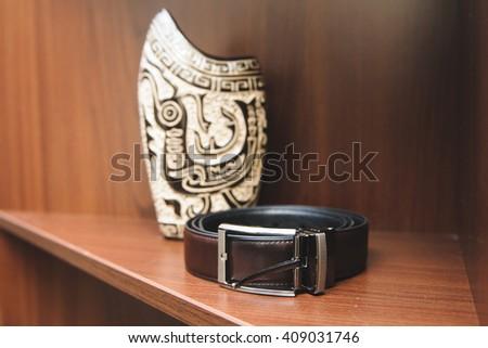 male leather belt on shelf with vase - stock photo