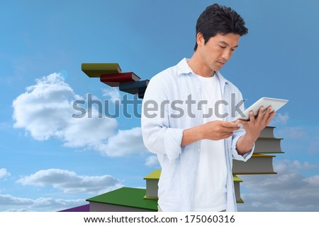 Male looking at his tablet computer against book steps against sky - stock photo