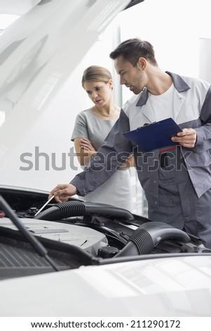 Male maintenance engineer explaining car engine to female customer in repair shop - stock photo