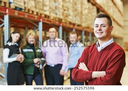 male manager and workers in warehouse - stock photo