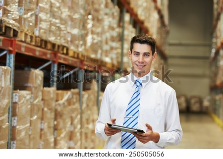 male manager man worker standing in big modern warehouse with tablet computer - stock photo