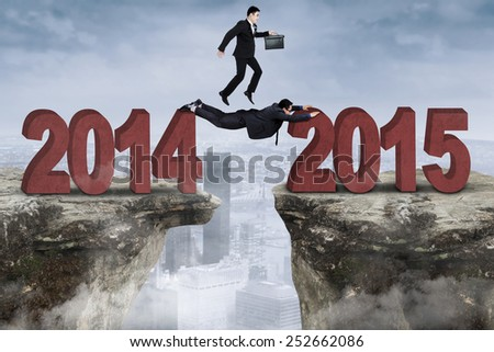 Male manager with his employee work together to through a gap from number 2014 to 2015 - stock photo