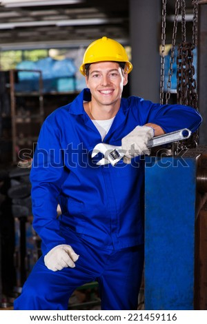 male manual worker holding spanner in factory - stock photo