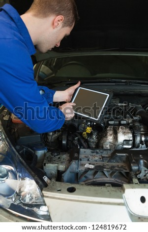 Male mechanic by car with open hood using tablet computer - stock photo