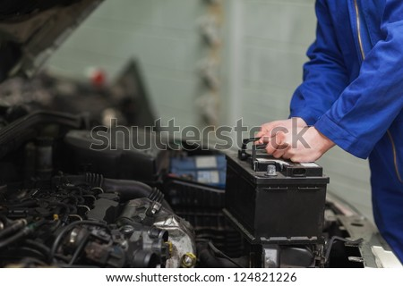 Male mechanic changing car battery - stock photo