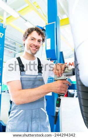 Male mechanic changing car tire or tyre in workshop - stock photo