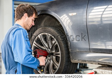 Male mechanic changing wheel on car with pneumatic wrench in garage - stock photo