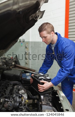 Male mechanic checking car battery in workshop - stock photo