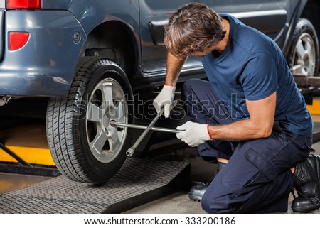Male mechanic fixing car tire with rim wrench at garage - stock photo