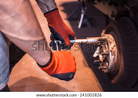 Male mechanic hands in gloves tightening the nuts using wrench. Mending, repair car in workshop. - stock photo