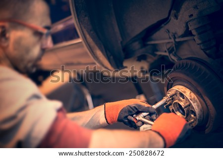 Male mechanic in gloves tightening the nuts using wrench. Mending, repair car in workshop. - stock photo