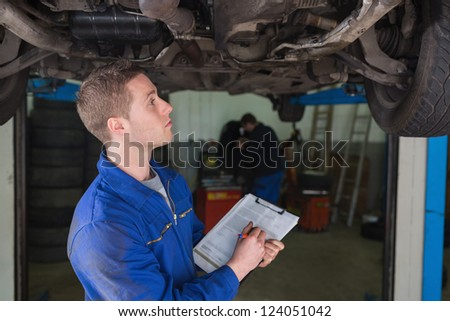 Male mechanic under car preparing checklist in workshop - stock photo