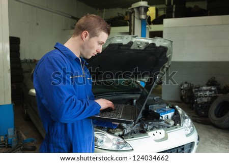 Male mechanic using laptop with car in background