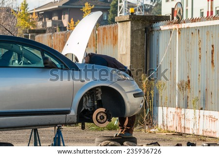 Male mechanic working on a car - stock photo