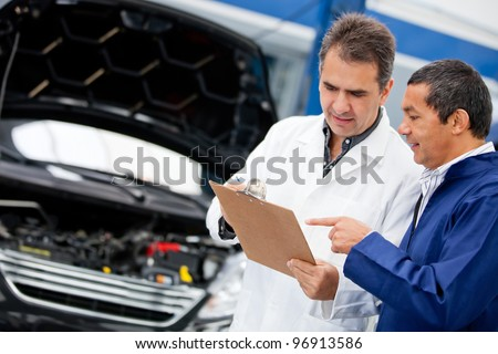 Male mechanics talking about fixing a car - stock photo