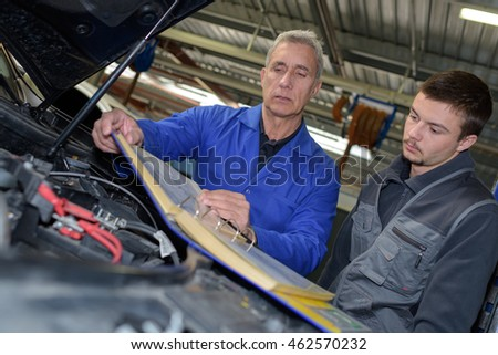 male mechanics working on car engine