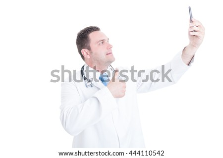 Male medic or doctor taking selfie and showing thumb up isolated on white background