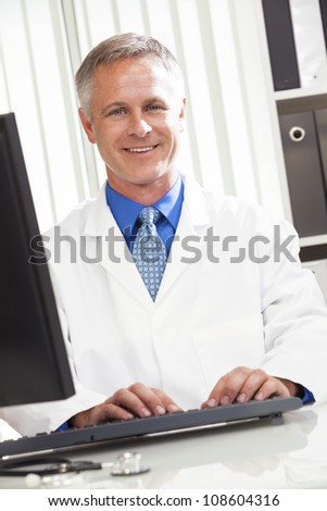 Male medical doctor using computer in his hospital office
