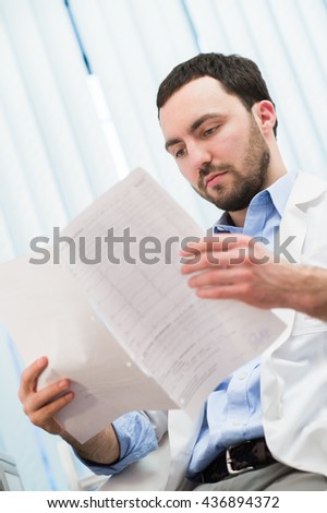 Male medicine doctor checking something at his papers. Medical care, insurance, prescription, paper work or career concept. Physician ready to examine patient and help. - stock photo