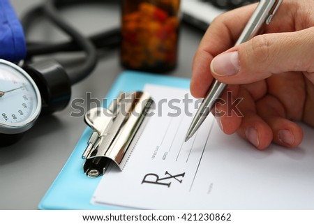 Male medicine doctor hand write prescription to patient at worktable with jar of pills in background. Panacea, life save, prescribing treatment, legal drug store concept. Empty form ready to be used - stock photo