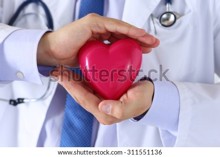 Male medicine doctor hands holding and covering red toy heart closeup. Medical help, cardiology care, health, prophylaxis, prevention, insurance, surgery and resuscitation concept - stock photo