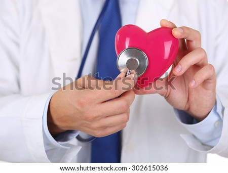 Male medicine doctor holding red heart and putting stethoscope head close to it closeup. Medical help, cardiology care, health, prophylaxis, prevention, insurance, surgery and resuscitation concept - stock photo