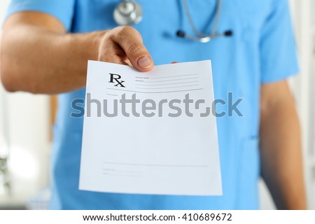 Male medicine doctor in blue uniform hold and give prescription to patient closeup. Panacea and life save, prescribe treatment, legal drug store, contraception concept. Empty form ready to be used - stock photo