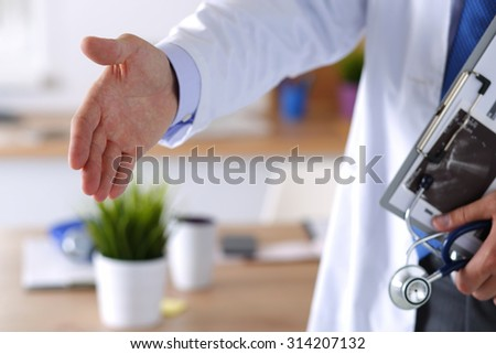 Male medicine doctor offering hand to shake in office closeup. Greeting and welcoming gesture. Medical cure and tests advertisement concept. Physician ready to examine patient - stock photo