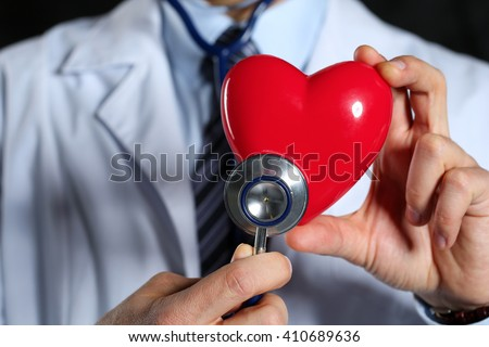 Male medicine doctor wearing hold in hands red toy heart and stethoscope closeup black background. Cardio therapeutist, physician make cardiac physical, heart rate measure, arrhythmia concept - stock photo