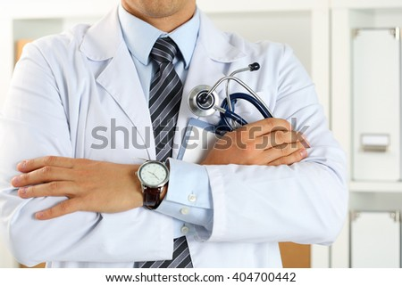 Male medicine therapeutist doctor hands crossed on his chest holding stethoscope in office closeup. Medical help or insurance concept. Physician is waiting for patient to examine - stock photo
