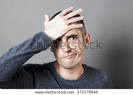 male mistake concept - confused young dark man pouting, holding his head, embarrassed, having regret, texture effects in studio - stock photo
