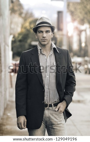 Male model posing on street in trendy casual outfit and hat - stock photo