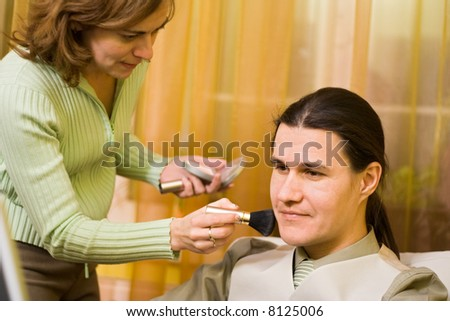 Male model receiving makeup from a woman
