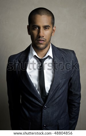 Male model stands posing in his suit and tie - stock photo