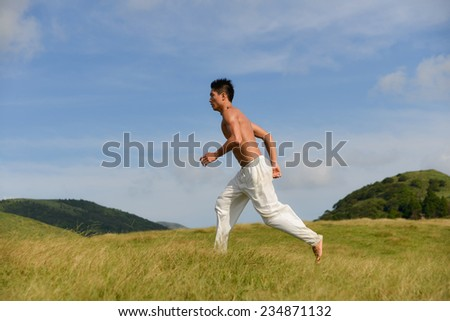 male model with muscles is running on summer meadow - lovely sunset light  - stock photo