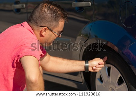 Male motorist checking the condition of a tyre - stock photo
