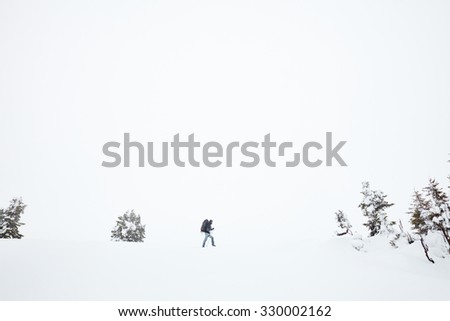 Male mountain climber with huge backpack and trekking poles having hard winter hiking trip after blizzard in Austrian Alps - stock photo