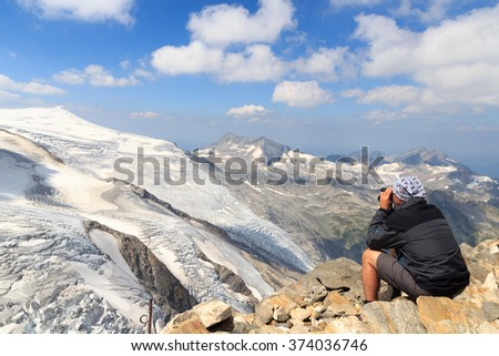 Male mountaineer looking at mountain glacier panorama view with binoculars  - stock photo