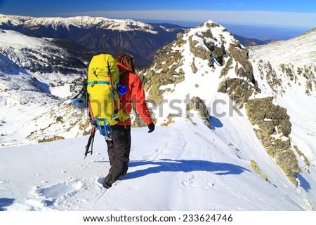 Male mountaineer on sunny snow covered mountain ridge - stock photo