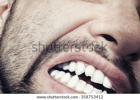 Male mouth with bared teeth close-up - stock photo