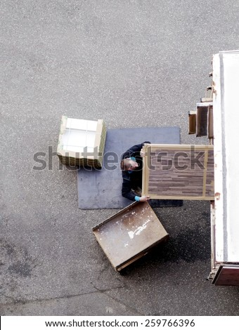 Male mover unload furniture and boxes from moving truck. Situation with moving house worker, manually download the furniture from a back of a truck. View from above. - stock photo