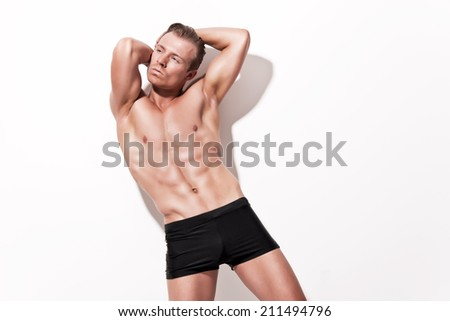 Male muscled underwear model wearing black shorts. Blonde hair. Against white wall.