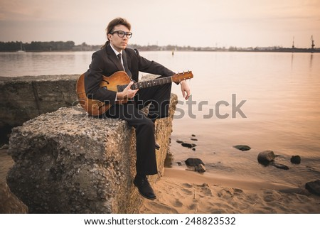 Male musician and his guitar on shore - stock photo