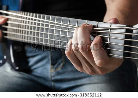 male musician playing on six-string bass guitar - stock photo