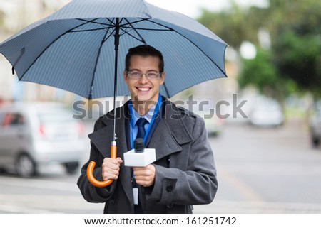 male news reporter holding umbrella and live broadcasting in the rain - stock photo